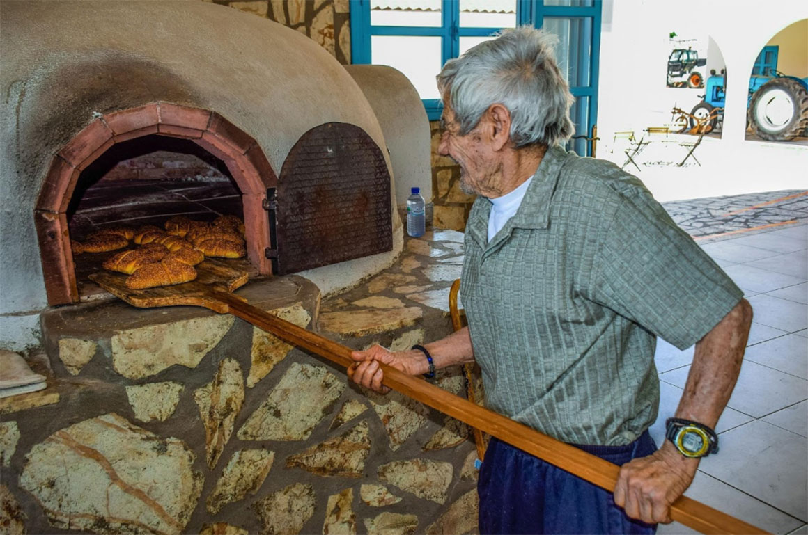 Male baker pulling bread out of a stone oven with a wooden baker's peel