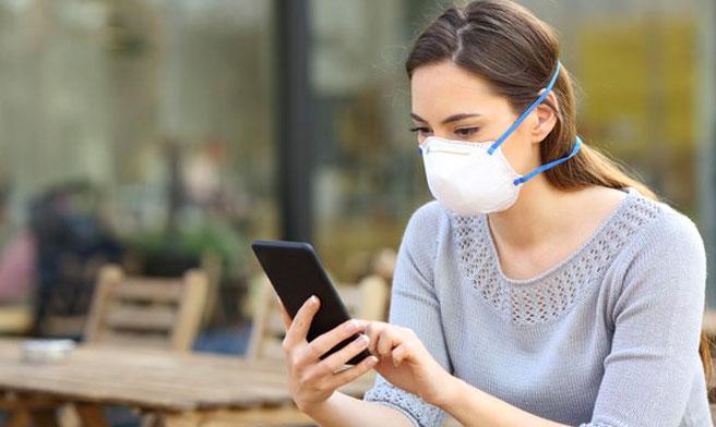 Woman wearing mask using phone, iStock